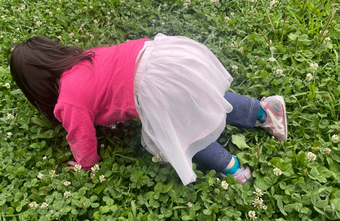 雨で濡れた雑草の上で遊ぶ子ども