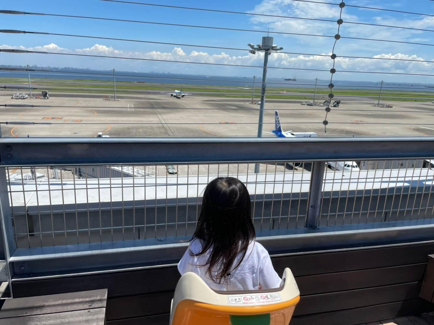 飛行機を見つめる子ども
